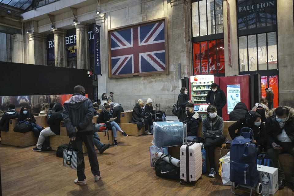 Passengers wearing face mask wait next to the Eurostar Terminal at Gare du Nord train station in Paris, Monday Dec. 21, 2020. France is banning all travel from the U.K. for 48 hours in an attempt to make sure that a new strain of the coronavirus in Britain doesn't reach its shores. (AP Photo/Lewis Joly)