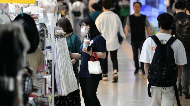 PHOTO: People wearing face masks walk through an underground shopping area in Seoul on May 6, 2020. (Jung Yeon-Je/AFP via Getty Images)