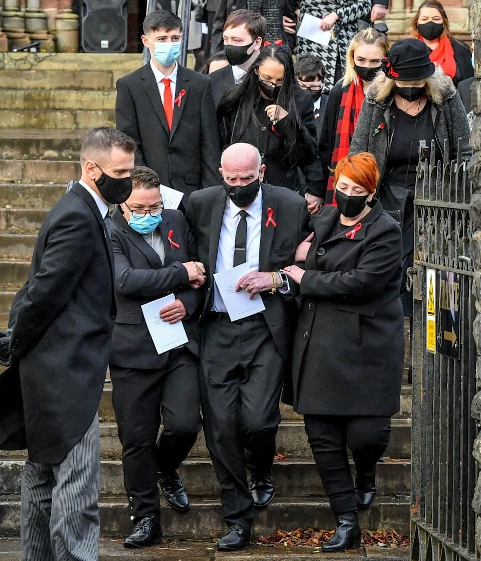 David Lewis, centre, husband to Gladys and father to Darren and Dean Lewis, is helped out of church by mourners - Ben Birchall/PA Wire