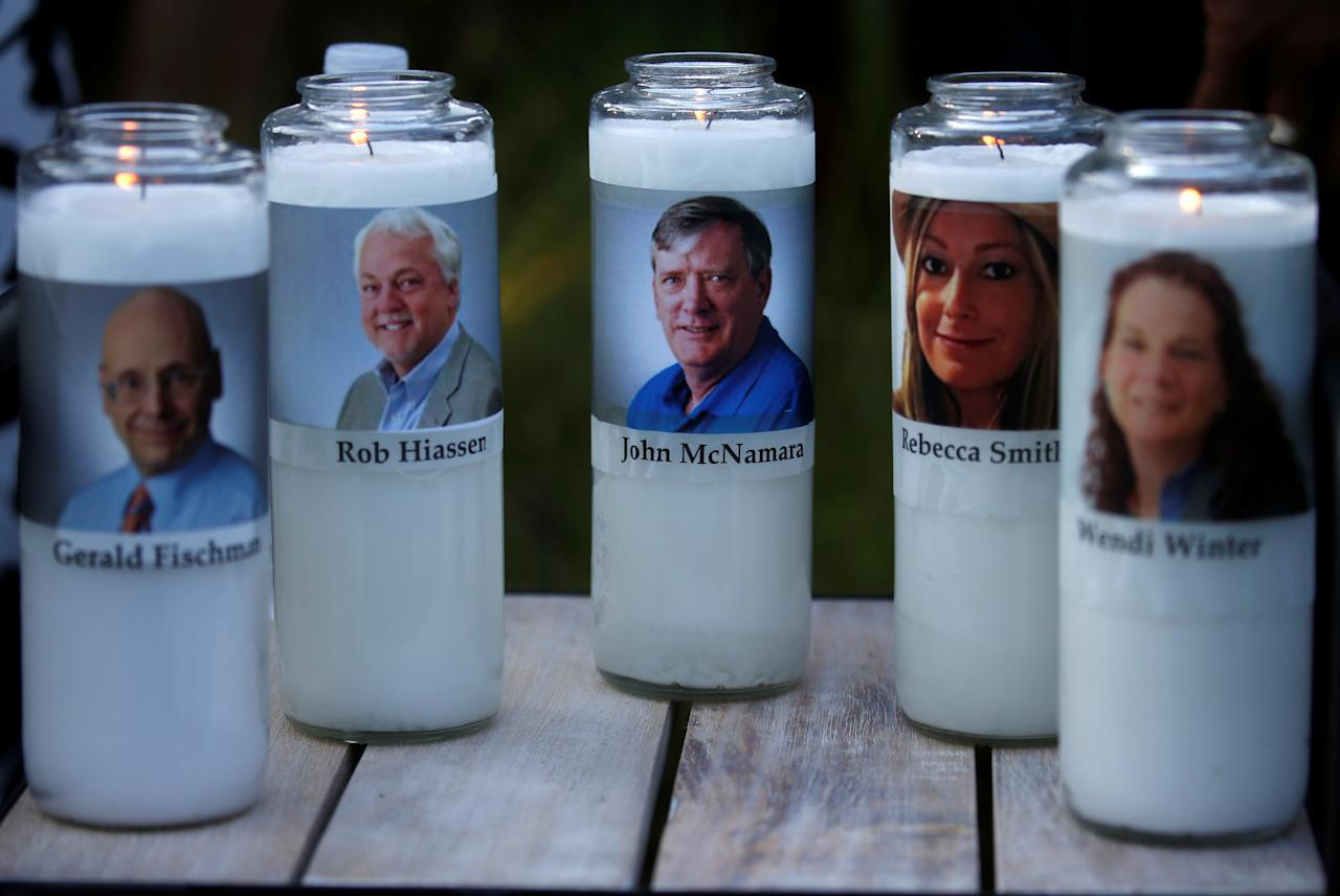 Candles representing the slain journalists of Capital Gazette sit on display during a candlelight vigil held near the Capital Gazette the day after a gunman killed five people inside the newspaper's building in Annapolis Md