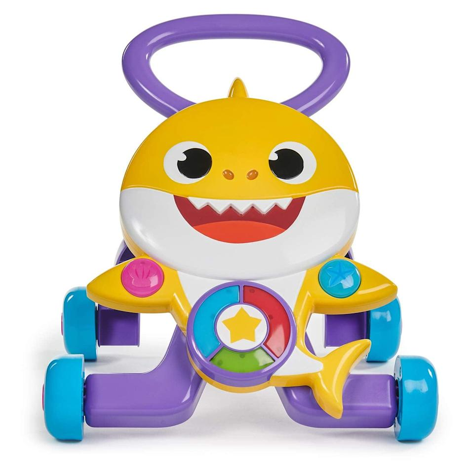 """<p>Your little one who's 12 months or older can take their very first steps with this <a href=""""https://www.popsugar.com/buy/Pinkfong-Baby-Shark-Melody-Walker-511972?p_name=Pinkfong%20Baby%20Shark%20Melody%20Walker&retailer=amazon.com&pid=511972&price=40&evar1=moms%3Aus&evar9=45808433&evar98=https%3A%2F%2Fwww.popsugar.com%2Fphoto-gallery%2F45808433%2Fimage%2F45808445%2FToddlers-Learning-Walk&list1=toy%20fair%2Ckid%20shopping&prop13=api&pdata=1"""" class=""""link rapid-noclick-resp"""" rel=""""nofollow noopener"""" target=""""_blank"""" data-ylk=""""slk:Pinkfong Baby Shark Melody Walker"""">Pinkfong Baby Shark Melody Walker</a> ($40) that lights up and sings.</p>"""