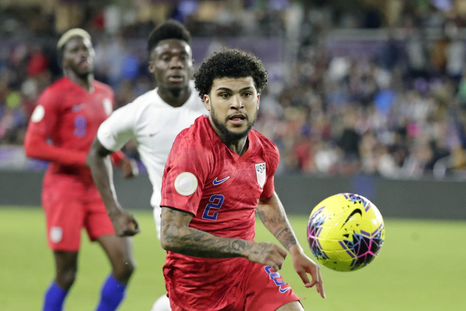 U.S. defender DeAndre Yedlin, right, goes after the ball in front of Canada midfielder Alphonso Davies, center, as forward Gyasi Zardes, left, watches during the second half of a CONCACAF Nations League soccer match Friday, Nov. 15, 2019, in Orlando, Fla. (AP Photo/John Raoux)