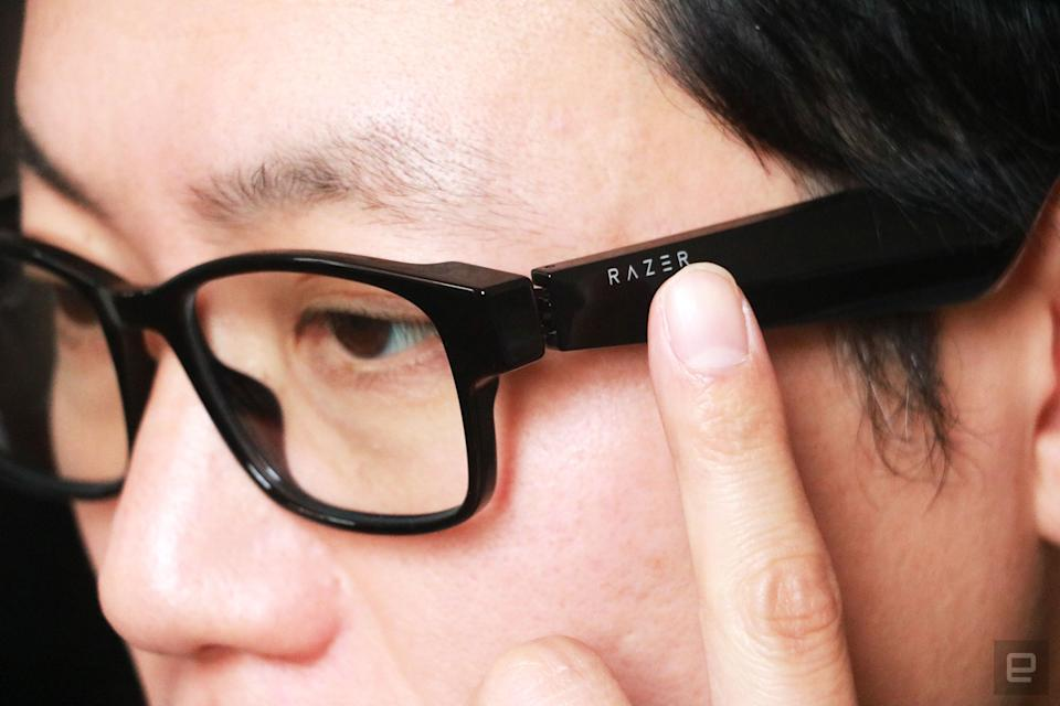 Razer Anzu smart glasses review photo. Close up of the left side profile of a man wearing the Razer smart glasses with his left index finger touching the left arm right below the Razer logo.