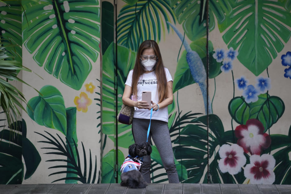 A woman takes a picture of her dog outside the Eastwood mall in Quezon city, Philippines as government eases restrictions after a decline in Coronavirus cases in the country on Thursday, Oct. 14, 2021. Several businesses were allowed to reopen in the next days as the country tries to revive the economy which have suffered due to lockdowns to prevent the spread of COVID-19. (AP Photo/Aaron Favila)