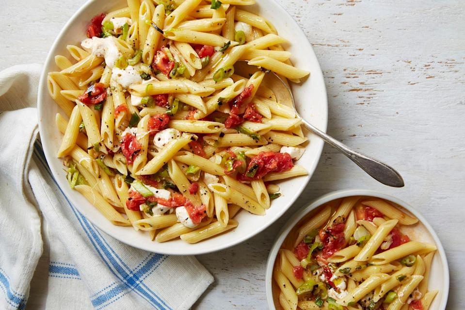"""Grilling the tomatoes concentrates their flavor slightly while still leaving them fresh enough to make a light, juicy sauce. Studded with cubes of fresh mozzarella, this dish is a summery crowd-pleaser. <a href=""""https://www.epicurious.com/recipes/food/views/pasta-with-grilled-tomato-and-scallion-sauce-51241220?mbid=synd_yahoo_rss"""" rel=""""nofollow noopener"""" target=""""_blank"""" data-ylk=""""slk:See recipe."""" class=""""link rapid-noclick-resp"""">See recipe.</a>"""