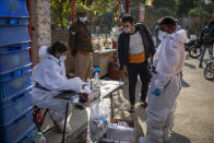 An Indian man registers his name before undergoing COVID-19 testing during during random testing of people in front of a shop at Delhi-Noida border on the outskirts of New Delhi, India, Saturday, Nov. 21, 2020. (AP Photo/Altaf Qadri)