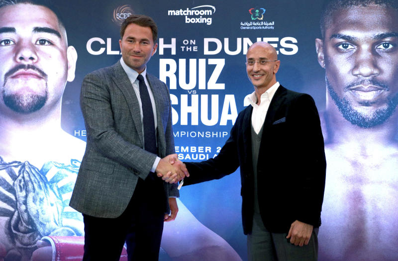 Boxing promoters Eddie Hearn and managing partner of Skill Challenge Entertainment Omar Khalil shake hands, during a press conference at The Savoy Hotel, London, Monday, Aug. 12, 2019. Anthony Joshua's promoters say his world heavyweight title rematch against Andy Ruiz Jr. will take place in Diriyah, Saudi Arabia, on Dec. 7. (Ian Walton/PA via AP)