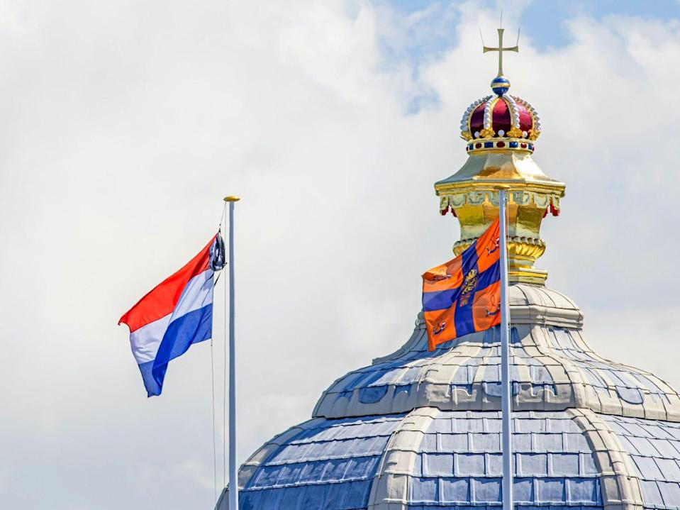 A backpack hangs on the same pole as the Dutch flag in front of the Palace Huis ten Bosch.