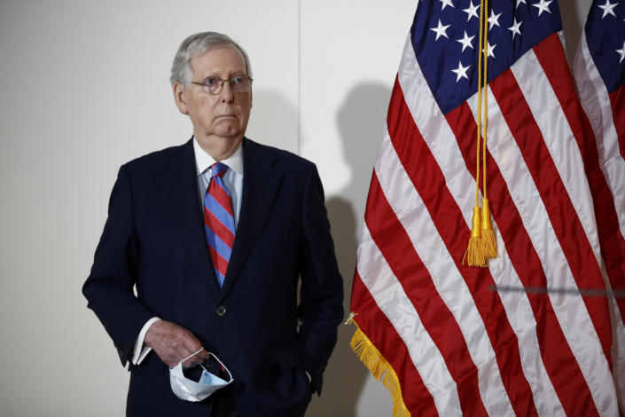 Senate Majority Leader Mitch McConnell of Ky., holds a face mask used to protect against the spread of the new coronavirus as he attends a news conference on Capitol Hill in Washington, Tuesday, May 12, 2020. (AP Photo/Patrick Semansky)