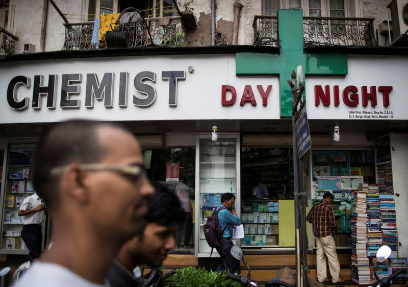 FILE PHOTO: FILE PHOTO: People walk past a chemist shop at a market in Mumbai