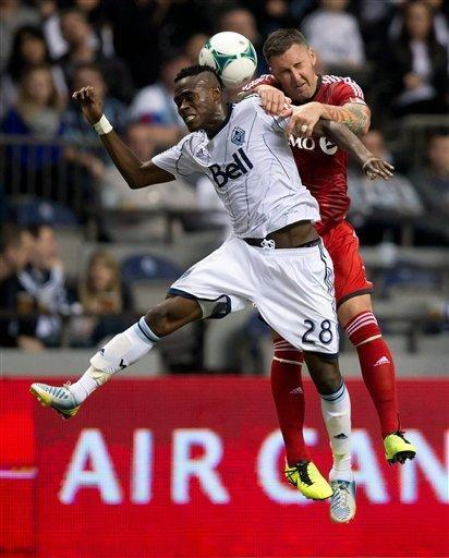 Vancouver Whitecaps' Gershon Koffie, left, of Ghana, and Toronto FC's Danny Califf vie for the ball during the second half of an MLS soccer game in Vancouver, British, Columbia, Saturday, March 2, 2013. (AP Photo/The Canadian Press, Darryl Dyck)