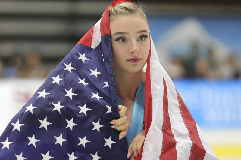 Flag-draped Amber Glenn, of the United States, skates around the rink after her third-place finish at the U.S. International Figure Skating Classic on Saturday, Sept. 21, 2019, in Salt Lake City. (AP Photo/Rick Bowmer)