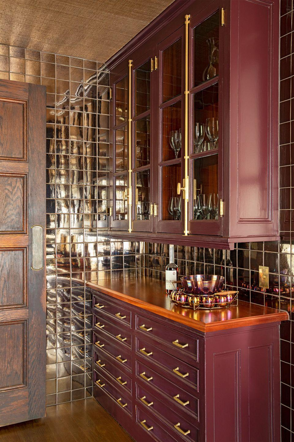 """<p>Paint the cabinets a red wine-inspired hue in an adjacent butler's pantry or entertaining space to set the mood for a tasting. We're digging the smokey mirrored tiles in this space by <a href=""""https://birgittepearcedesign.com/"""" rel=""""nofollow noopener"""" target=""""_blank"""" data-ylk=""""slk:Birgitte Pearce Design"""" class=""""link rapid-noclick-resp"""">Birgitte Pearce Design</a>—they elevate the entire experience. </p>"""