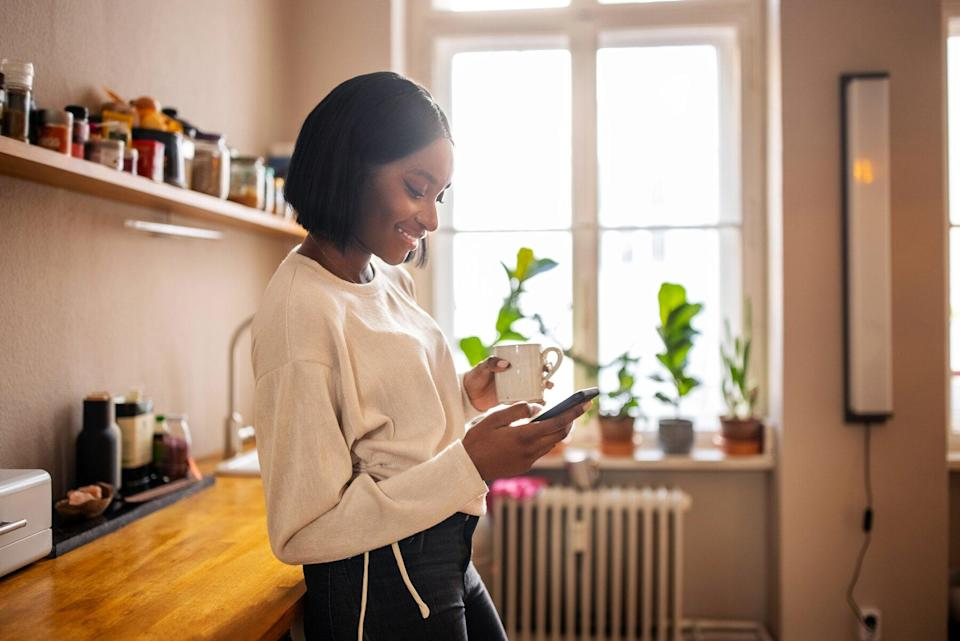 Woman standing in the kitchen holding a cup of coffee and texting on her cell phone. Woman using a mobile phone at home.
