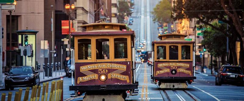 Classic view of historic traditional Cable Cars riding on famous California Street in San Francisco