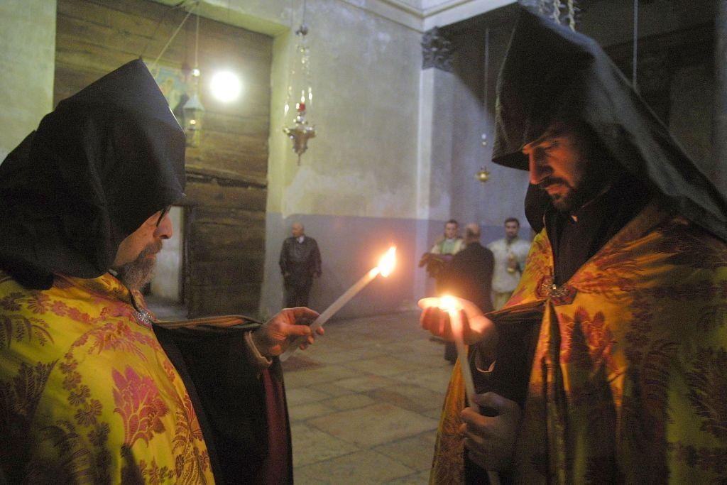 BETHLEHEM, WEST BANK:  Armenian priests light candles as they make the last preparations before the noon service in the Church of the Nativity in Bethlehem. File photo: 2003