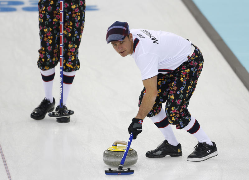 Norway skip Thomas Ulsrud, wearing rose-painting knickers and a patterned flat cap, sweeps ahead of the stone during curling training at the 2014 Winter Olympics, Saturday, Feb. 8, 2014, in Sochi, Russia. (AP Photo/Robert F. Bukaty)