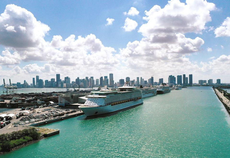 In an aerial view, Explorer of the Seas (front), a Royal Caribbean cruise ship, along with other cruise ships are docked at PortMiami as the cruise line industry waits to begin operations again on May 26, 2021 in Miami, Florida (Getty Images)