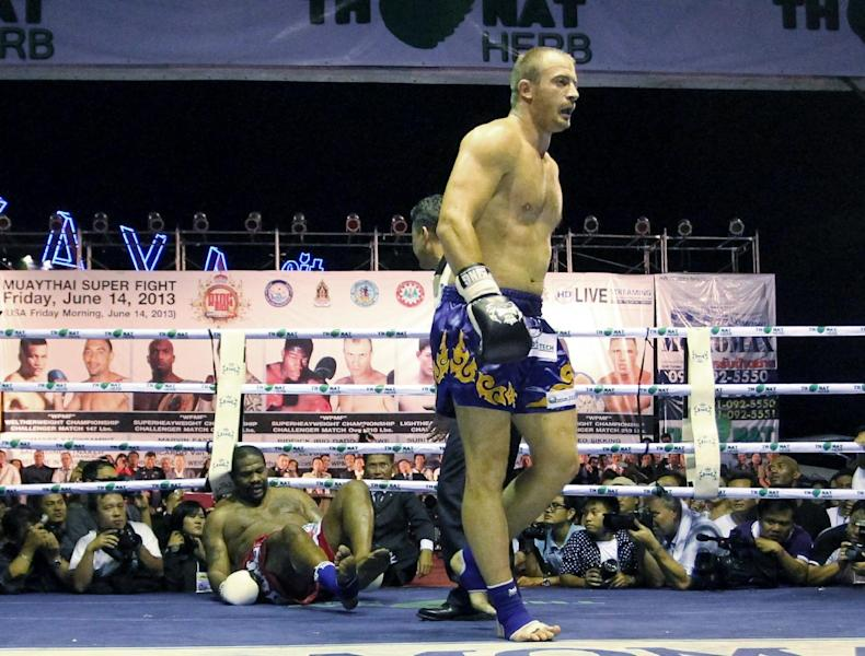 Former heavyweight boxing champion Riddick Bowe of the U.S., left, lies on the canvas after he was knocked down by Levgen Golovin of Russia, right, during their World Muay Thai or Kick Boxing Super Heavyweight Championships fight in Pattaya, Thailand Friday, June 14, 2013. Golovin won the bout in a second round knockout by kicking on the leg. (AP Photo/Apichart Weerawong)