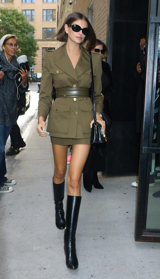 """<a href=""""https://www.teenvogue.com/tag/kaia-gerber?mbid=synd_yahoo_rss"""">The supermodel</a> hit the streets in a militar-inspired green jacket, wide belt, and miniskirt, and paired her look with knee-high black boots and sunglasses."""