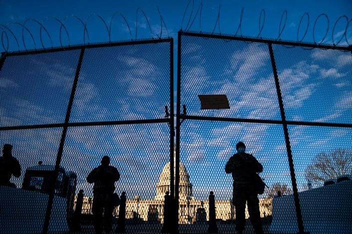 WASHINGTON, DC - JANUARY 16: National Guard troops stand behind security fencing with the dome of the U.S. Capitol Building behind them, on Saturday, Jan. 16, 2021 in Washington, DC. After last week's riots and security breach at the U.S. Capitol Building, the FBI has warned of additional threats in the nation's capital and across all 50 states. (Kent Nishimura / Los Angeles Times)