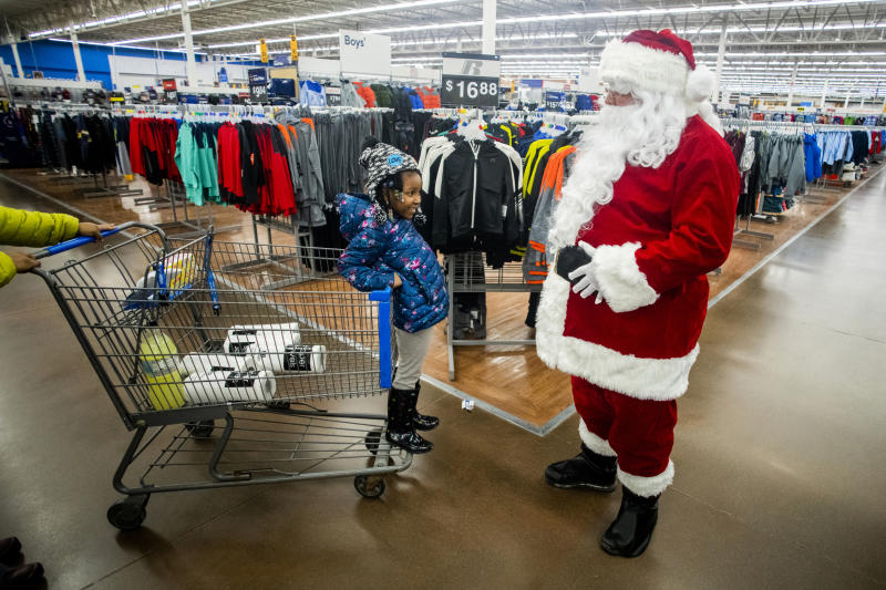 Jordyn Barnett, 5, of Grand Blanc, smiles as she sticks out her belly holding onto her mother's shopping cart while running into Santa Claus at Walmart, Monday, Dec. 16, 2019, in Grand Blanc Township, Mich. (Jake May/The Flint Journal via AP)