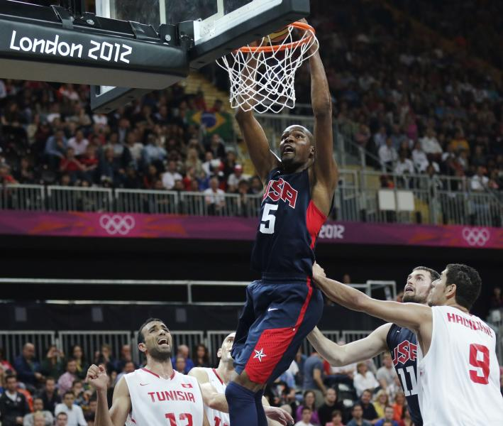 USA's Kevin Durant (5) slams a dunk over Tunisia's Makram Ben Romdhane, left, and Mohamed Hadidane (9) during a men's basketball game at the 2012 Summer Olympics, Tuesday, July 31, 2012, in London. (AP Photo/Charles Krupa)