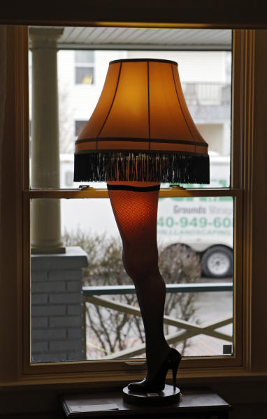 "In this Nov. 21, 2013, photo, a leg lamp is framed in the window of the house in Cleveland where much of the 1983 movie ""A Christmas Story"" was filmed. A surge of visitors is expected to tour the restored house, and purchase a miniature lamp or two at the gift shop, on the 30th anniversary of the quirky holiday film. (AP Photo/Mark Duncan)"