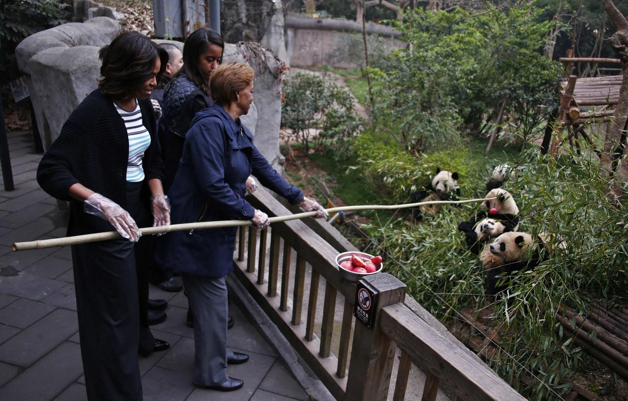 U.S. first lady Michelle Obama (L) and her mother Marian Robinson (R) feed apple to giant pandas as daughter Malia looks on during their visit at Giant Panda Research Base in Chengdu, Sichuan province, March 26, 2014. REUTERS/Petar Kujundzic (CHINA - Tags: ANIMALS POLITICS SOCIETY TPX IMAGES OF THE DAY)