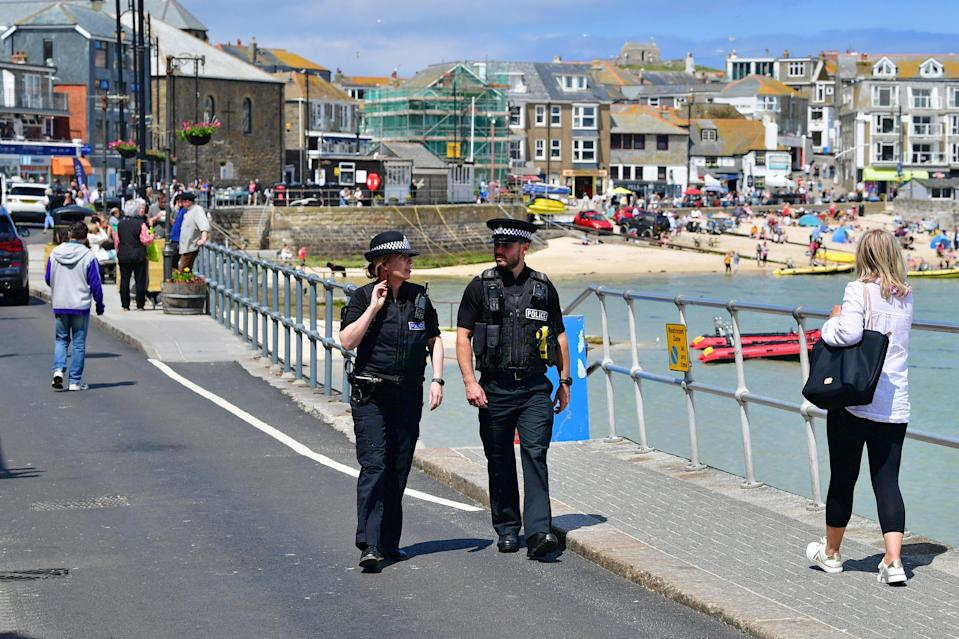 Police officers walk along the seafront in St Ives (PA)