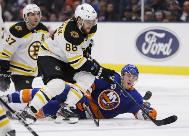 Boston Bruins' David Pastrnak (88) fights for control of the puck with New York Islanders' Anthony Beauvillier during the second period of an NHL hockey game Tuesday, March 19, 2019, in Uniondale, N.Y. (AP Photo/Frank Franklin II)