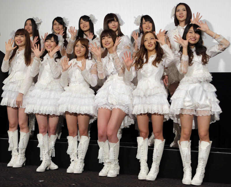"""In this Friday, Feb. 1, 2013 file photo, hugely popular Japanese girl band AKB48 members, from left in first row, Haruna Kojima, Mayu Watanabe, Minami Takahashi, Mariko Shinoda, Tomomi Itano and Rie Hitahara, and others, pose for photographers at the opening premiere of their new film """"Documentary of AKB48 No Flower Without Rain"""" in Tokyo, one day after a group member shaved her head and issued a tearful videotaped apology for violating the megagroup's no-dating rule. The spectacle has sparked debate in Japan over whether the band AKB48 exerts too much control over its performers. Minami Minegishi made the video, posted on AKB48's website, after the 20-year-old was caught by a gossip magazine coming out of her boyfriend's apartment. AKB48 says it forbids its members from dating to project a clean image and signal their devotion to the group and their mostly male fans. (AP Photo/Itsuo Inouye, File)"""