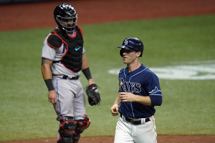 Tampa Bay Rays' Joey Wendle, right, scores in front of Miami Marlins catcher Jorge Alfaro on a bases loaded walk by starting pitcher Pablo Lopez to Kevin Kiermaier during the fourth inning of a baseball game Friday, Sept. 4, 2020, in St. Petersburg, Fla. (AP Photo/Chris O'Meara)