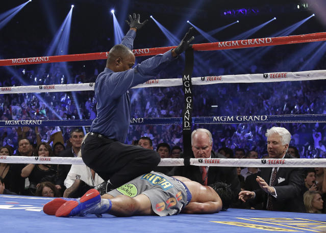 Referee Kenny Bayless calls the fight as he kneels over Manny Pacquiao, from the Philippines, after he was knocked out by Juan Manuel Marquez, from Mexico, during their WBO world welterweight fight Saturday, Dec. 8, 2012, in Las Vegas. (AP Photo/Julie Jacobson)