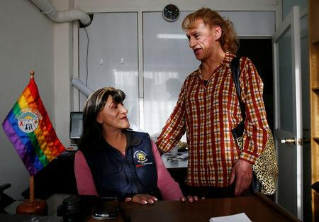 Pamela Valenzuela (L) and her friend Carla chat as they pose for a photo after Pamela became the first transgender Bolivian citizen to receive a new identity card, following a new law that allows transgender people to register under their assumed gender, in La Paz, Bolivia, September 7, 2016. REUTERS/David Mercado?