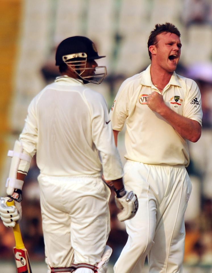Australian cricketer Doug Bollinger (R) celebrate the wicket of Indian cricketer Rahul Dravid (L) during the fourth day of the first Test between India and Australia in Mohali on October 4, 2010. India, needing 216 to win in their second innings, were wobbling at 55-4 at stumps on the penultimate day, with Hilfenhaus finishing with 3-22 off seven sharp overs. AFP PHOTO/Dibyangshu SARKAR (Photo credit should read DIBYANGSHU SARKAR/AFP/Getty Images)