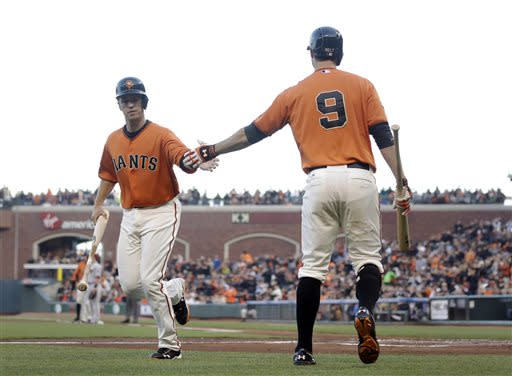 San Francisco Giants' Buster Posey, left, is greeted by Brandon Belt (9) after scoring on a single from Hunter Pence during the first inning of a baseball game Friday, July 19, 2013, in San Francisco. (AP Photo/Marcio Jose Sanchez)