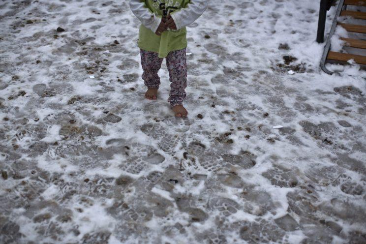 A Syrian refugee child walks barefoot on frozen ground at the refugee camp of Ritsona about 86 kilometers north of Athen on Jan. 11, 2017. Photo from The Canadian Press