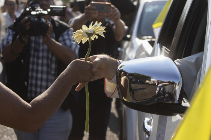 Monsignor Franco Coppola, the Vatican's diplomat to Mexico, receives a flower as he arrives to meet families and celebrate Mass in Aguililla, a town that has been cut off by warring cartels in Michoacan state, Mexico, Friday, April 23, 2021. State police and soldiers were sent in to restore order earlier this month, but cartels responded by parking hijacked trucks across roads to block them, as well as digging deep trenches across roadways. (AP Photo/Armando Solis)