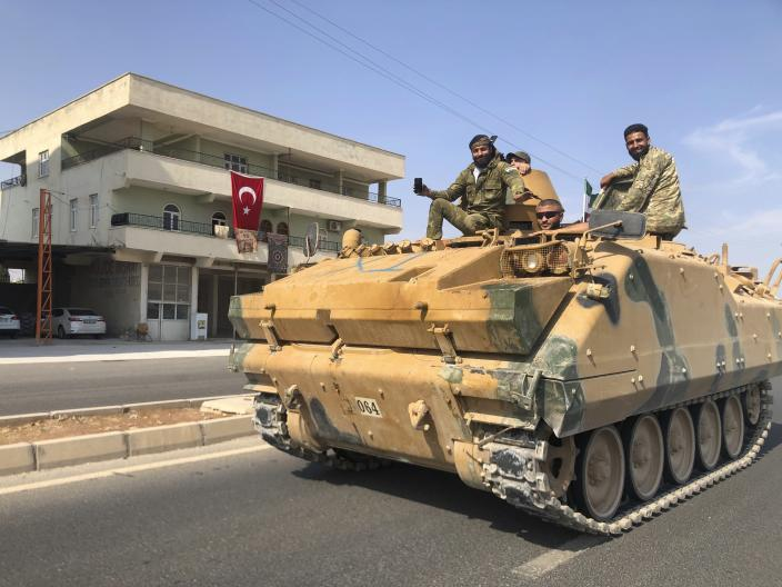 In this Friday, Oct. 18, 2019 photo, Turkish-backed Syrian opposition fighters ride atop their armored personnel carrier to cross the border into Syria, in Akcakale, Sanliurfa province, southeastern Turkey. Turkish President Recep Tayyip Erdogan wants Syrian government forces to move out of areas near the Turkish border so it can resettle up to 2 million refugees there, his spokesman told The Associated Press on Saturday, adding that Erdogan will raise the issue in talks next week with Syria's ally, Russian President Vladimir Putin. (AP Photo/Mehmet Guzel)
