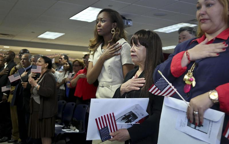 """Immaculee Ilibagiza, fourth from right, center, join new immigrants in the pledge allegiance, during the U.S. Citizenship and Immigration Services (USCIS) naturalization ceremony on Wednesday, April 17, 2013 in New York.  Ilibagiza, author of the best seller """"Left to Tell, Discovering God Amidst the Rwandan Holocaust,"""" addressed fellow immigrants with her story of hiding in a 3-by-4 foot bathroom with seven other women and girls before fleeing the 1994 Rwandan genocide, which claimed more than 500,000 lives. (AP Photo/Bebeto Matthews)"""