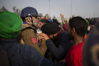 A protesting farmer pleads in front of a police officer to let them pass through a barricade at at the Delhi-Uttar Pradesh state border, India, Tuesday, Jan. 26, 2021. Tens of thousands of farmers drove a convoy of tractors into the Indian capital as the nation celebrated Republic Day on Tuesday in the backdrop of agricultural protests that have grown into a rebellion and rattled the government. (AP Photo/Altaf Qadri)