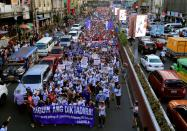 """Women's rights activists display a streamer that reads """"Down with Dictatorship"""" as they march along a busy street during a celebration of the International Women's Day in Quiapo city, Metro Manila"""