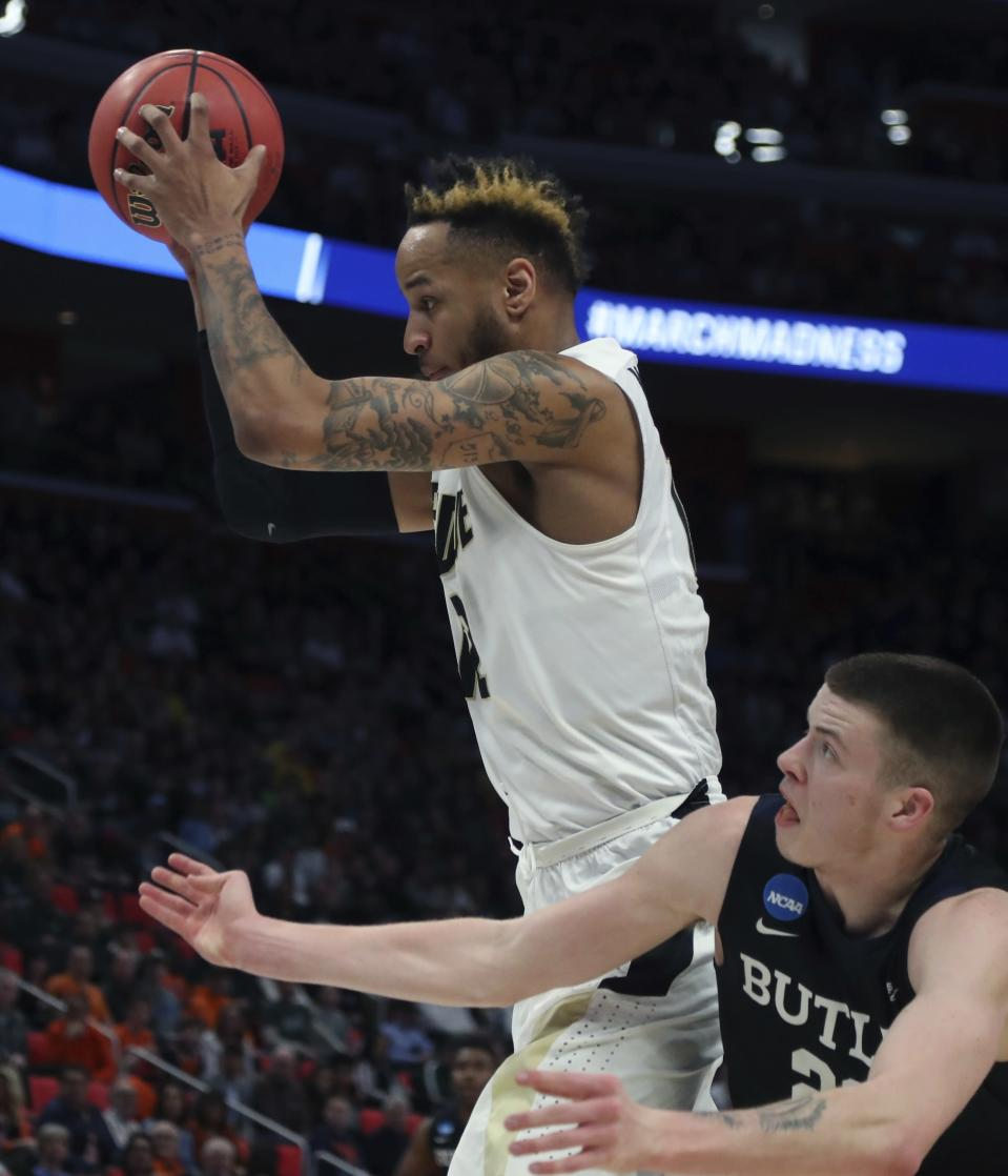 Purdue forward Vincent Edwards, top, pulls down a rebound next to Butler guard Sean McDermott during the second half of a second round game in the NCAA college basketball tournament, Sunday, March 18, 2018, in Detroit. (AP Photo/Carlos Osorio)