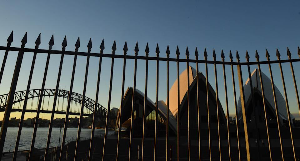 The Sydney Harbour Bridge and the Sydney Opera House is seen behind a high fence at sunset in Sydney. Source: AAP