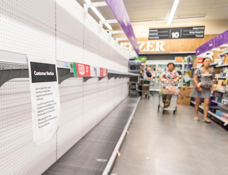 Customers looks at empty shelves at a supermarket in Brisbane.