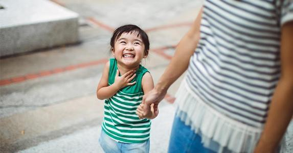 Smiling child holding mother's hand | Images By Tang Ming Tung/Getty Images