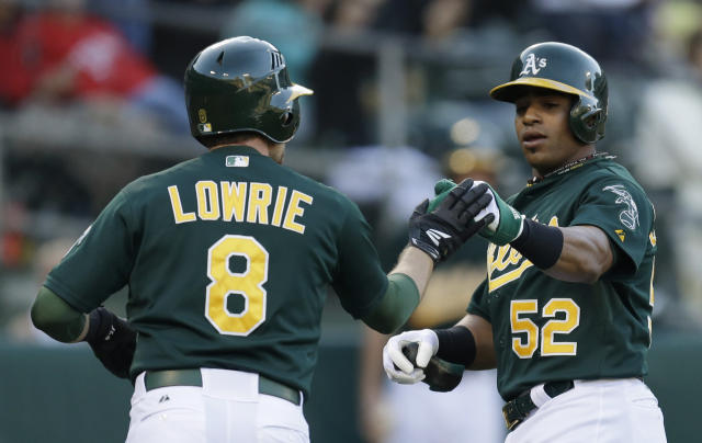 Oakland Athletics' Jed Lowrie (8) and Yoenis Cespedes (52) celebrate after scoring against the Texas Rangers in the first inning of a baseball game, Friday, Aug. 2, 2013, in Oakland, Calif. Both men scored on a two run double by A's Brandon Moss. (AP Photo/Ben Margot)