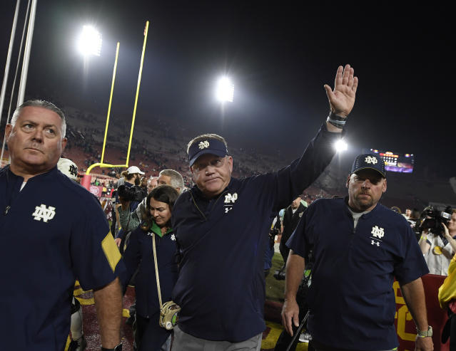Notre Dame's Brian Kelly waves as he walks off the field at Los Angeles Memorial Coliseum after defeating the USC Trojans on Saturday. (AP)
