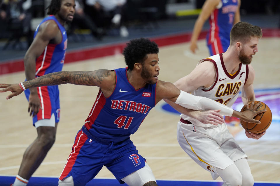 Detroit Pistons forward Saddiq Bey (41) reaches in on Cleveland Cavaliers forward Dean Wade during the second half of an NBA basketball game, Monday, April 19, 2021, in Detroit. (AP Photo/Carlos Osorio)